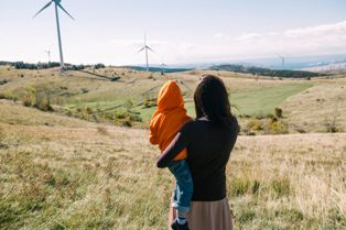 24194980 - mother holding her son in nature. wind turbines in the background.